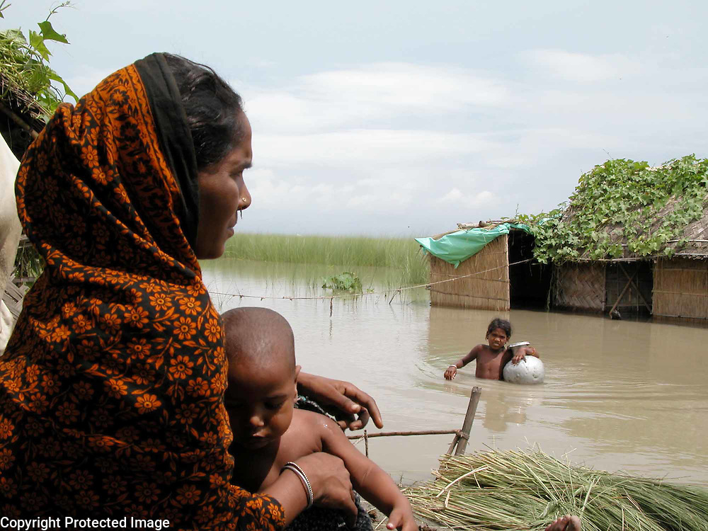 AKHTAR BANO, An  village woman carries with her baby, ONE YEAR OLD ZAHIRUL ISLAM AT A HIGH SAFER PLACE WHILE HER HOUSE IS GOING  under water AT SIALMARI village, about 325 kilometers (203 miles) southwest of Gauhati, capital of northeastern Indian state of Assam, Friday, July 11, 2003. Floods and mudslides in the northeastern states of Assam has killed at least 28 people over the past week and uprooted more than 500,000 from their homes, while 25 lakhs render homeless. (AP Photo/Shib Shankar Chatterjee)
