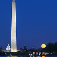Historic Washington DC landmark photography image displaying the United States Capitol and the Washington Memorial with a rising full moon reflection in the Licoln Memorial Reflection Pool in Washington DC, Maryland.   <br />