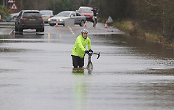 © Licensed to London News Pictures. 24/12/2013<br /> A cyclist walking through the flood water with his bike.<br /> London Road A224  Polhill in Halstead, Kent is closed with cars abandoned in 4 feet of rain water overnight.<br /> The UK  has woken up to trees and electricity cables down following a night of gale-force winds and torrential rain.<br /> Photo credit :Grant Falvey/LNP