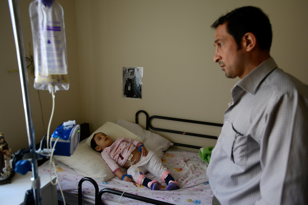 Walaa Matti, 43, checks his two year old daughter's condition in her bedroom. Shortly after arriving in the United States from Iraq his youngest daughter Irana fell ill. Doctors said it was just a stomach flu until she collapsed. She was then diagnosed with an unusual brain infection. She underwent surgery and is now following long-term medical treatment. She is limp, sleeps most of the day and must be fed intravenously. Walaa spends most of his time caring for his daughter and family and has little time to look for work. His daughter's illness and his lack of knowledge of how things function in the United States has made their resettlement process extremely difficult.<br />