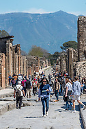 Female tourist walking down center of street in Pompeii looking at map; tourists, mountain and ruins behind her.
