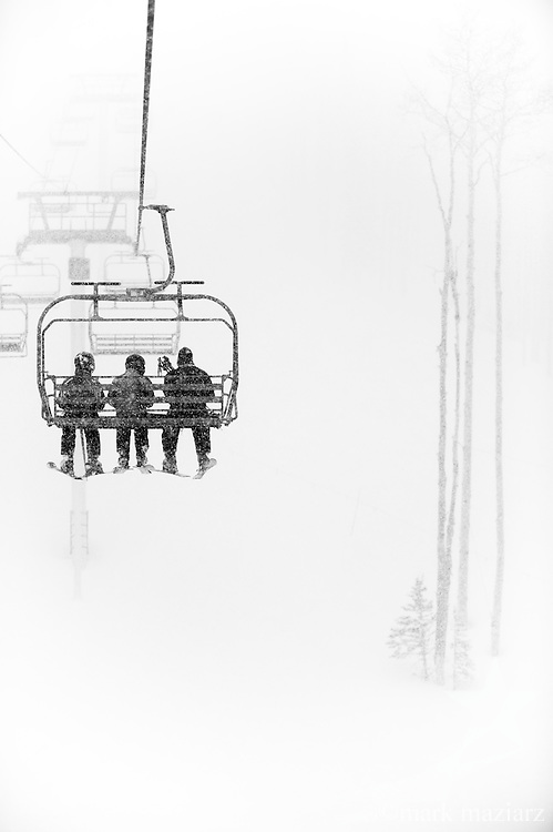 Three skiers riding up Dreamscape chairlift at Canyons Resort, Park City, Utah during fresh snowfall.