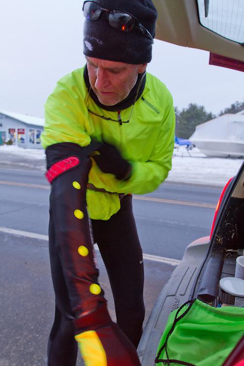 Gary Allen runs from Maine to Washington DC, putting on Glimmer Gear as dusk approaches along Bath Road near Brunswick