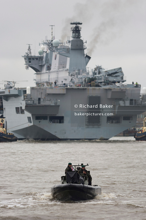 Royal Marines in a Rigid Hull Inflatable Boat (RIB), accompanying HMS Ocean (L12) upstream on the River Thames towards Greenwich ahead of a major security exercise in preparation for the 2012 Olympic Games. Oceanis anamphibious assault ship(orlanding platform helicopter), the sole member of her class and the Royal Navy's largest ship. She then berthed at Greenwich in east London, close to the main Olympic venue where it will act as a launch pad for eight army Lynx helicopters from 661 Squadron and a base for Royal Marine snipers, able to shoot at the engines of fast-moving targets. It is the final phase of the exercise named Olympic Guardian, which began earlier this week in Weymouth, England and in the airspace over the capital. During theactual Olympics in July, Ocean will be moored in Greenwich to provide logistics support, accommodation to 9 Assault SquadronRoyal Marines and a helicopter landing site. HMS (Her Majestys Ship) Ocean was constructed in the mid 90sat a cost of £234million, the 203.4m (667 ft) long, 21,500 tonnes. .