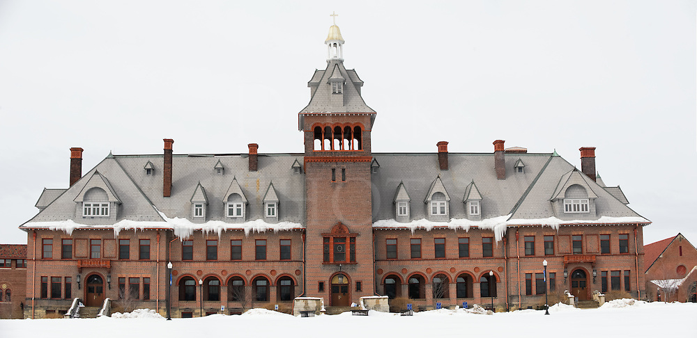 Large school building in Victorian architectural style, bell tower, steep roof, winter snow and large icicles, stitched from two images in Photoshop to make panoramic, Mt Aloysius College, Cresson, Pennsylvania, PA, USA.
