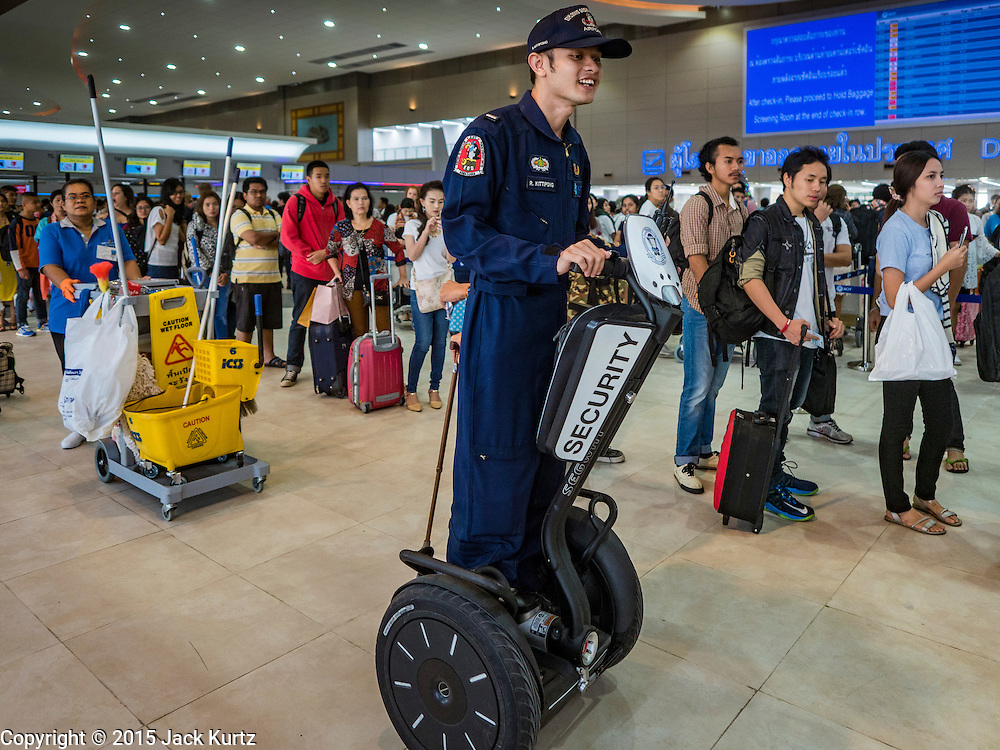"24 DECEMBER 2015 - BANGKOK, THAILAND:  A member of a Thai police bomb squad uses a Segway to patrol the new domestic terminal at Don Muang (also spelled Don Mueang) International Airport. The new terminal had its ""soft"" opening Dec. 24. Don Muang is the airport used by low cost airlines serving Bangkok and is now the largest airport in the world for low cost carriers. In 2014, more than 21million passengers used Don Muang. Don Muang International Airport is the oldest airport in Asia and one of the oldest airports in the world. It started functioning as an airfield in 1914.    PHOTO BY JACK KURTZ"