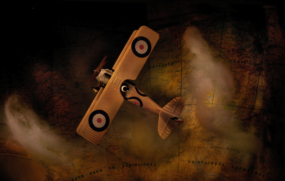 A toy aeroplane flying over a map with British markings