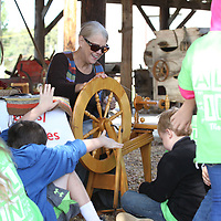 Jeanette Stone shows area students how pioneers made cloth and other materials at the textiles boothe during Friday's Dogtrot Heritage Festival at Oren Dunn Museum.