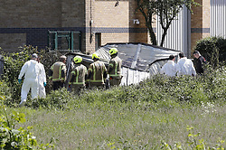 © Licensed to London News Pictures. 21/05/2019. London, UK. Forensics officers and fire fighters are seen on waste land next to a metal shed near Feltham in west London where a body was discovered. Reports say the victim was found next to a burnt out metal corrugated shed in the early hours of this morning. Photo credit: Peter Macdiarmid/LNP