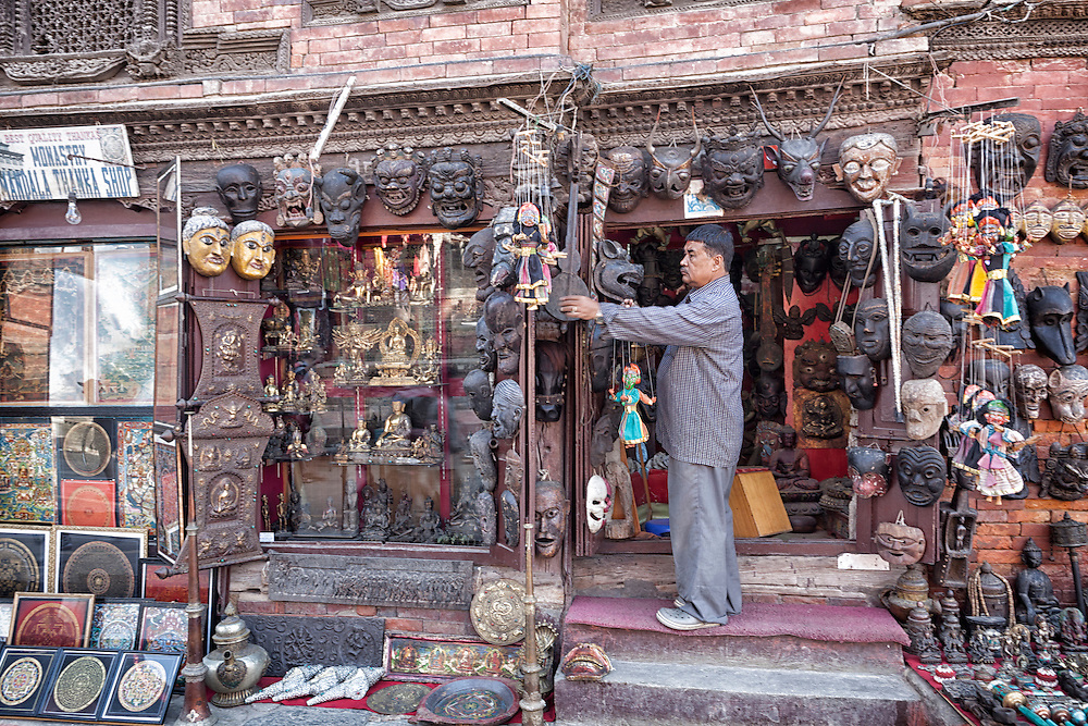 A man hangs a puppet outside his souvenir shop in Kathmandu's Durbar Square.