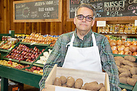 Portrait of a mature employee carrying potato box in front of vegetable stand in market