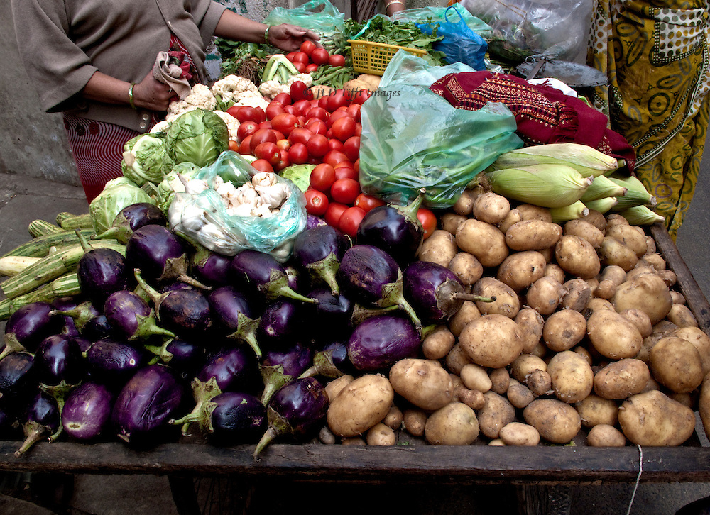 Attractive vegetable display on a cart in Ahmedabad, Gujarat, with hands of women customers turning over the merchandise.