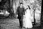 Louise & Greg walk through the church yard after their wedding