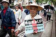 A old man holds a placard during the May Day rally in Tokyo on Monday, May 1, 2017, Thousands people participate demanding higher pays among other issues. 01/05/2017-Tokyo, JAPAN