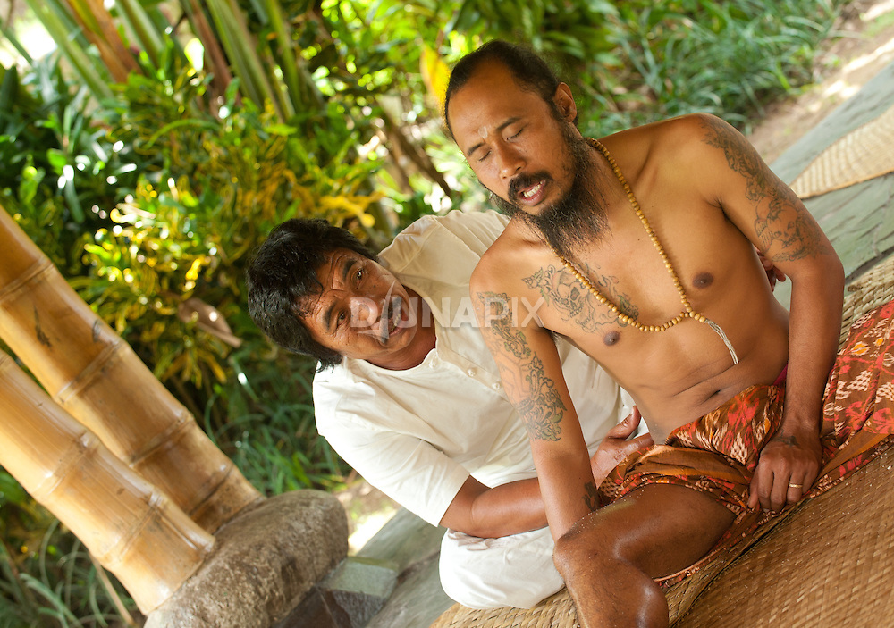 Balinese healers exchange treatments during a break.