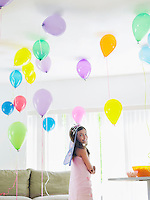 Young girl (7-9) standing in room full of balloons