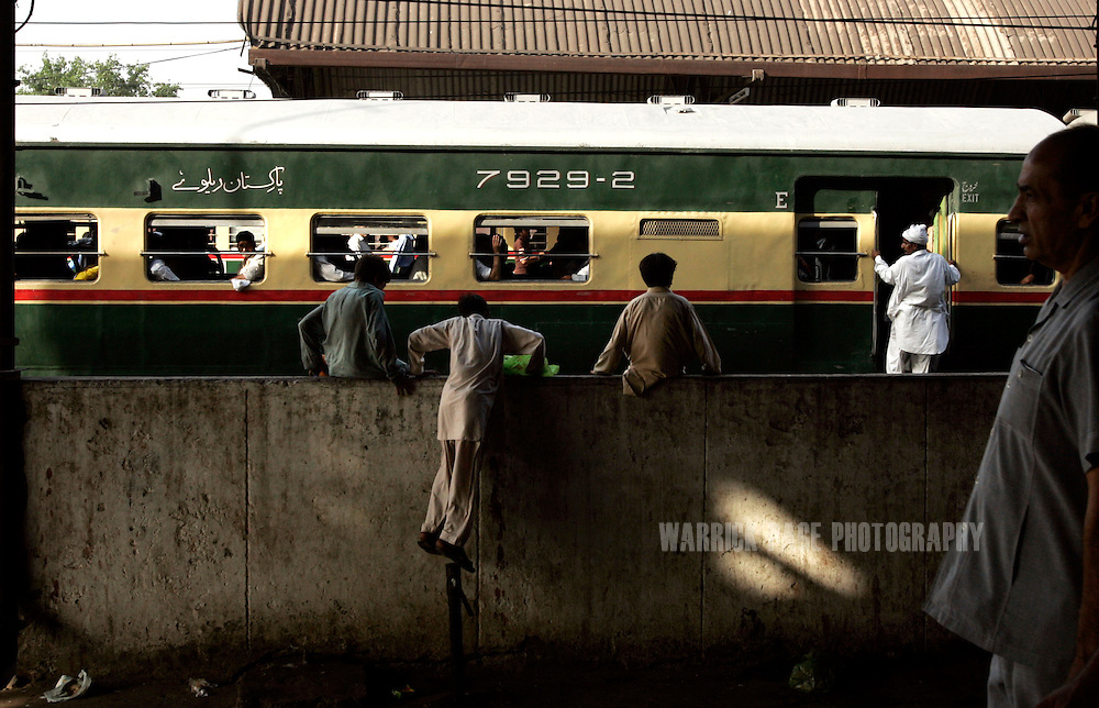 LAHORE, PAKISTAN - JUNE 5: Young boys watch trains depart Lahore rail station in Lahore, Pakistan, Tuesday, June 5, 2007. (Photo by Warrick Page)