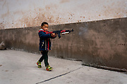 A boy walks the streets of Cizhong, Yunan, China during the lunar new year holidays holding a toy AK-47.