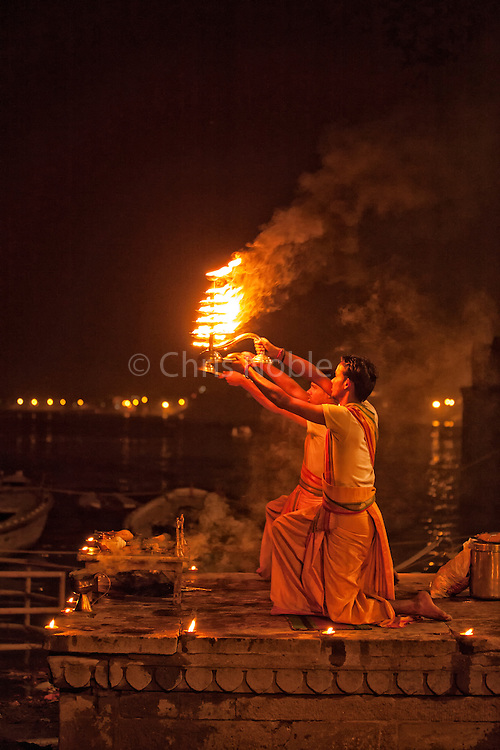 Two young men perform a fire puja ceremony at Lalita Ghat along the Ganges in Varanasi's Old City.