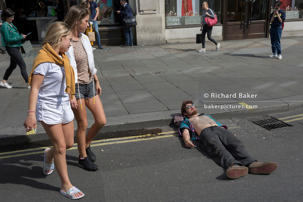 Passers-by look down on a young campaigner resting with his head on an Oxford Circus kerb on day 4 of protests by climate change environmental activists with pressure group Extinction Rebellion, on18th April 2019, in London, England.