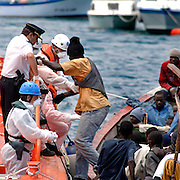 "Tenerife / Los Cristianos June 7, 2006 - would-be immigrants is helped to get off a boat at his arrival  at the canary islands  -  A fishing boat called ""Cayucos"" by the inhabitants of the island, with 85 would-be immigrants from West Africa intercepted by Spanish police of the coast of Tenerife in the Canary Islands are seen in an open wooden fishing vessel as they approach the port of Los Cristianos. They arrived on June, carrying 85 would-be immigrants, in the archipelago which has received more than 7,000 Africans so far this year, more than half to the tourist resort island of Tenerife. At least 1,000 more are believed to have died trying to make the sea crossing, mostly in small fishing boats"