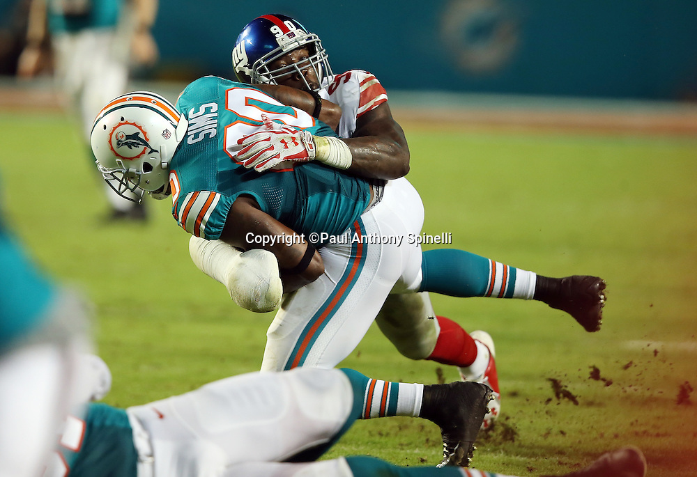 New York Giants defensive end Jason Pierre-Paul (90) tackles Miami Dolphins tight end Dion Sims (80), with his arm wrapped due to an injury, on a third down reception short of a first down, forcing a punt, during the NFL week 14 regular season football game against the New York Giants on Monday, Dec. 14, 2015 in Miami Gardens, Fla. The Giants won the game 31-24. (©Paul Anthony Spinelli)
