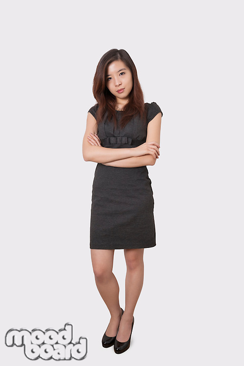 Full length portrait of beautiful young businesswoman standing arms crossed over white background