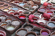 Detail of dye pits, Chouara tannery Fez, Morocco, pictured on February 25, 2009 in the evening. The Chouara tannery is the largest of the four ancient tanneries in the Medina of Fez where the traditional work of the tanners has remained unchanged since the 14th century. It is composed of numerous dried-earth pits where raw skins are treated, pounded, scraped and dyed. Tanners work in vats filled with various coloured liquid dyes derived from plant sources. Colours change every two weeks, poppy flower for red, mint for green, indigo for blue, chedar tree for brown and saffron for yellow. Fez, Morocco's second largest city, and one of the four imperial cities, was founded in 789 by Idris I on the banks of the River Fez. The oldest university in the world is here and the city is still the Moroccan cultural and spiritual centre. Fez has three sectors: the oldest part, the walled city of Fes-el-Bali, houses Morocco's largest medina and is a UNESCO World Heritage Site;  Fes-el-Jedid was founded in 1244 as a new capital by the Merenid dynasty, and contains the Mellah, or Jewish quarter; Ville Nouvelle was built by the French who took over most of Morocco in 1912 and transferred the capital to Rabat. Picture by Manuel Cohen.