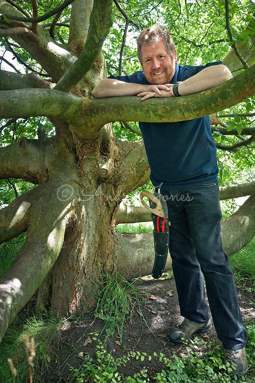 Tony Kirkham amongst branches of Zelkova carpinifolia (Caucasian elm) before pruning to shape at RBG Kew