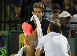 March 28, 2018 - Key Biscayne, Florida, United States - Juan Martin Del Potro, from Argentina, talking with a physiotherapist after feeling some pain during his quarter final match at the Miami Open. Del Potro defeated Raonic 5-7, 7-6(1), 7-6(3) in Miami, on March 28, 2018. (Credit Image: © Manuel Mazzanti/NurPhoto via ZUMA Press)