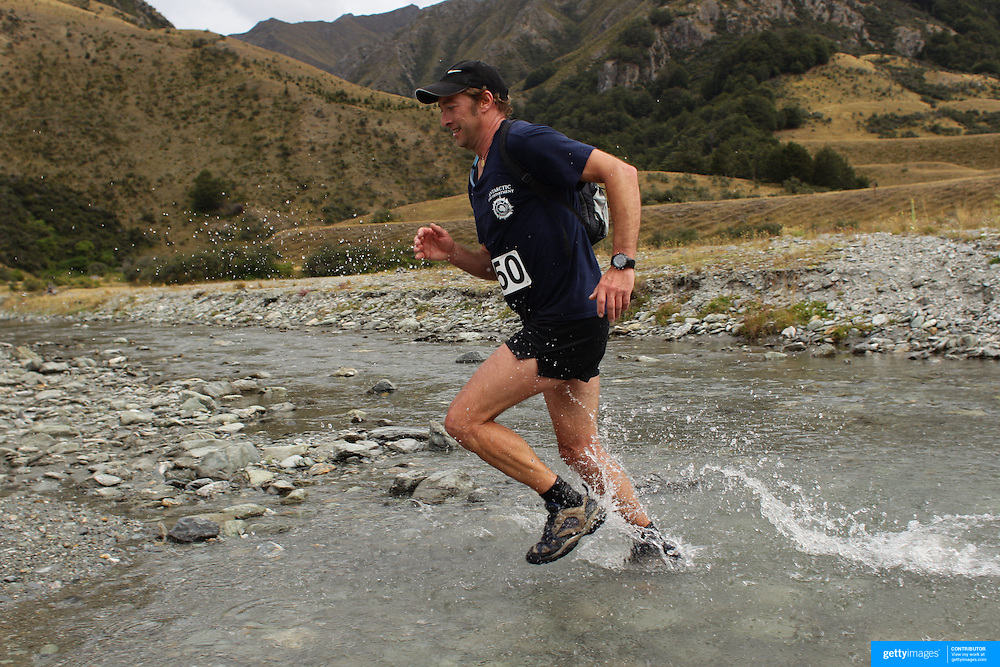 Runner Christophe Van Haute crosses Moke Creek on the Ben Lomond High Country Station during the Pure South Shotover Moonlight Mountain Marathon and trail runs. Moke Lake, Queenstown, New Zealand. 4th February 2012. Photo Tim Clayton