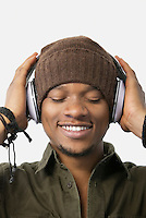 Close-up of relaxed young man listening music through headphones