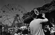 """Ferris Wheel and Merry-Go-Round, Father waving to Daughter. Coney Island, Brooklyn, New York City...Part of long-term (2005-2008) story """"I See A Darkness"""". New York, NY."""