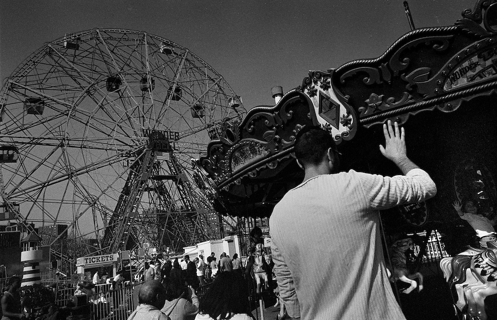 "Ferris Wheel and Merry-Go-Round, Father waving to Daughter. Coney Island, Brooklyn, New York City...Part of long-term (2005-2008) story ""I See A Darkness"". New York, NY."