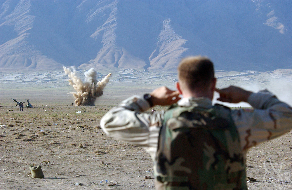 A soldier from the US Army 101st airborne plugs his ears as a mortar round explode on the Shamali plain during a traning exercise on July 14, 2002 near Bagram in Afghanistan. Coalition forces continue to train for missions as part of the ongoing Operation Enduring Freedom.