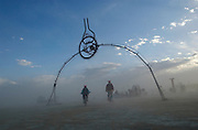 Cyclist ride under  a metal arch at the San Francisco based Camp Carp at the Burningman counter culture arts festival in the Black Rock Desert 100 miles north east of Reno, NV, Thursday, Sept 2, 2004.