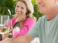 Couple holding wine glasses sitting at outdoor table