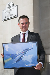 ROYAL MAIL - Minister of State for the Armed Forces Rt Hon Mark Lancaster TD MP holds a new stamp design featuring a Eurofighter Typhoon . London, March 20 2018.