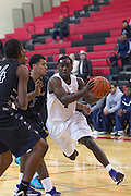 Cedar Ridge's DD Harris drives around Shoemaker's Parris Yerry Friday during the Leander ISD Tournament.  The Raiders beat the Grey Wolves 58-37 at Vista Ridge Gym.