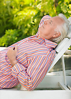 Man reclining on lounge chair outdoors side view