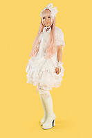 Full length portrait of young woman dressed as a doll over yellow background