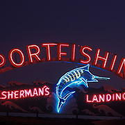 "Colorful neon sign,lit up at dusk, reading ""Sportsfishing, Fisherman's Landing"" at Pt Loma sports fishing establishment, H&M Landing in San Diego. Blue neon tuna is on the sign."