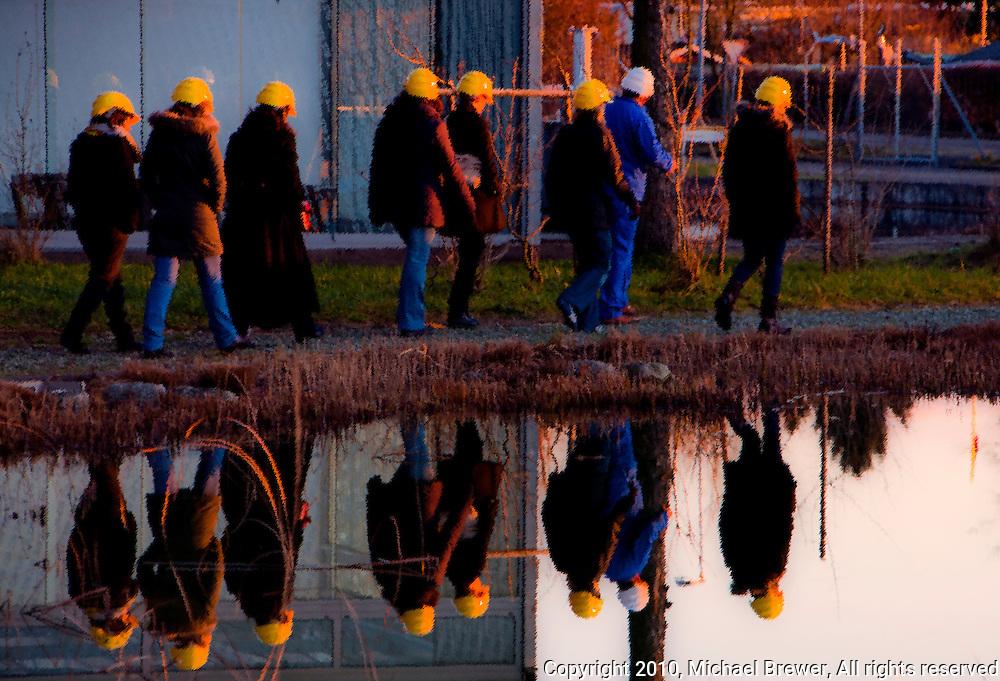 Tour group reflected in a treatment pond at sunset at Werdhölzli Sewage Treatment Plant, Zürich, Switzerland.