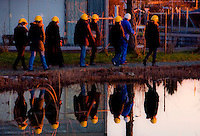 Tour group reflected in a treatment pond at sunset at Werdhölzli Sewage Treatment Plant, Zürich, Switzerland.