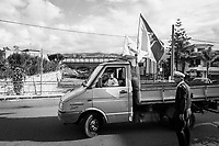 VILLAFRANCA TIRRENA, ITALY - 27 OCTOBER 2017: Angela Raffa (24), a  Five Star Movement (Italian: Movimento 5 Stelle, or M5S) candidate running for the Sicilian regional assembly, drives her family-run business truck with Sicilian and M5S flags, as she looks for a parking space just minutes before the arrival of M5S candidate Giancarlo Cancelleri, running for governor of Sicily in the upcoming Sicilan regional election, here in Villafranca Tirrena, Italy, on October 27th 2017.  Angela Raffa has a degree in Business, but hasn't found a job after a graduation. Since then, she works in her family-run construction business by driving a truck.<br /> <br /> The Sicilian regional election for the renewal of the Sicilian Regional Assembly and the election of the President of Sicily will be held on 5th November 2017.