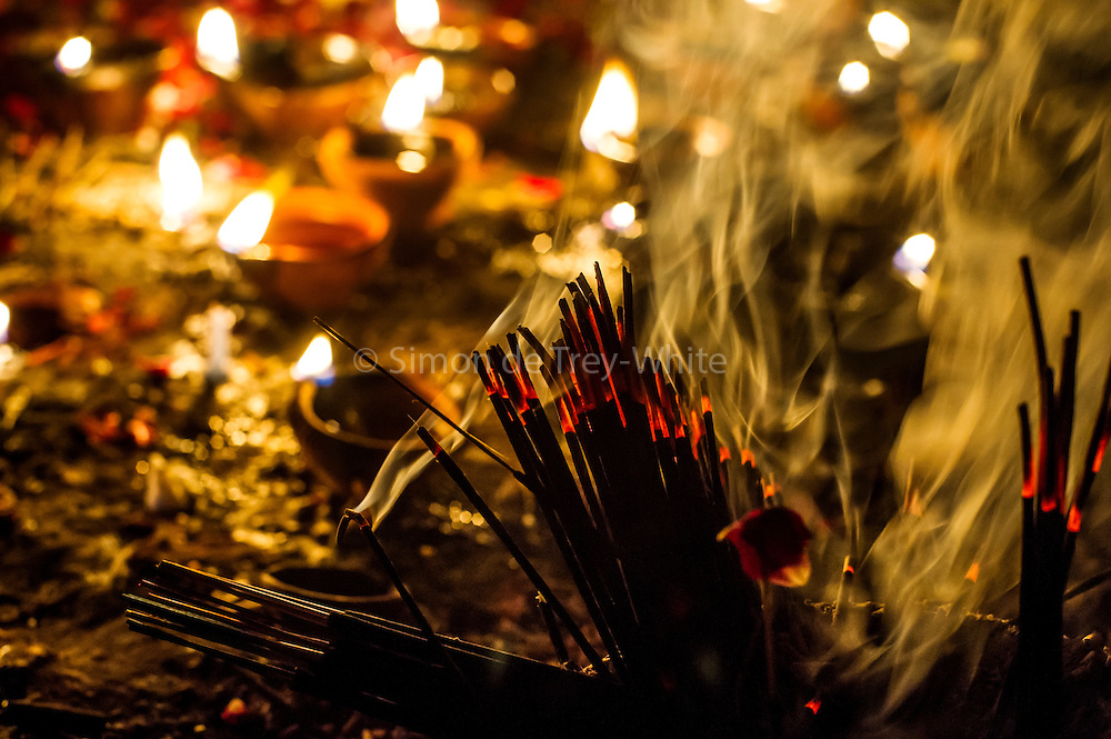 8th January 2015, New Delhi, India. Incense sticks and oil lamps left by believers hoping to get their wishes granted by Djinns burn in the ruins of Feroz Shah Kotla in New Delhi, India on the 8th January 2015<br /> <br /> PHOTOGRAPH BY AND COPYRIGHT OF SIMON DE TREY-WHITE a photographer in delhi<br /> + 91 98103 99809. Email: simon@simondetreywhite.com<br /> <br /> People have been coming to Firoz Shah Kotla to leave written notes and offerings for Djinns in the hopes of getting wishes granted since the late 1970's. Jinn, jann or djinn are supernatural creatures in Islamic mythology as well as pre-Islamic Arabian mythology. They are mentioned frequently in the Quran  and other Islamic texts and inhabit an unseen world called Djinnestan. In Islamic theology jinn are said to be creatures with free will, made from smokeless fire by Allah as humans were made of clay, among other things. According to the Quran, jinn have free will, and Iblīs abused this freedom in front of Allah by refusing to bow to Adam when Allah ordered angels and jinn to do so. For disobeying Allah, Iblīs was expelled from Paradise and called &quot;Shayṭān&quot; (Satan).They are usually invisible to humans, but humans do appear clearly to jinn, as they can possess them. Like humans, jinn will also be judged on the Day of Judgment and will be sent to Paradise or Hell according to their deeds. Feroz Shah Tughlaq (r. 1351&ndash;88), the Sultan of Delhi, established the fortified city of Ferozabad in 1354, as the new capital of the Delhi Sultanate, and included in it the site of the present Feroz Shah Kotla. Kotla literally means fortress or citadel.