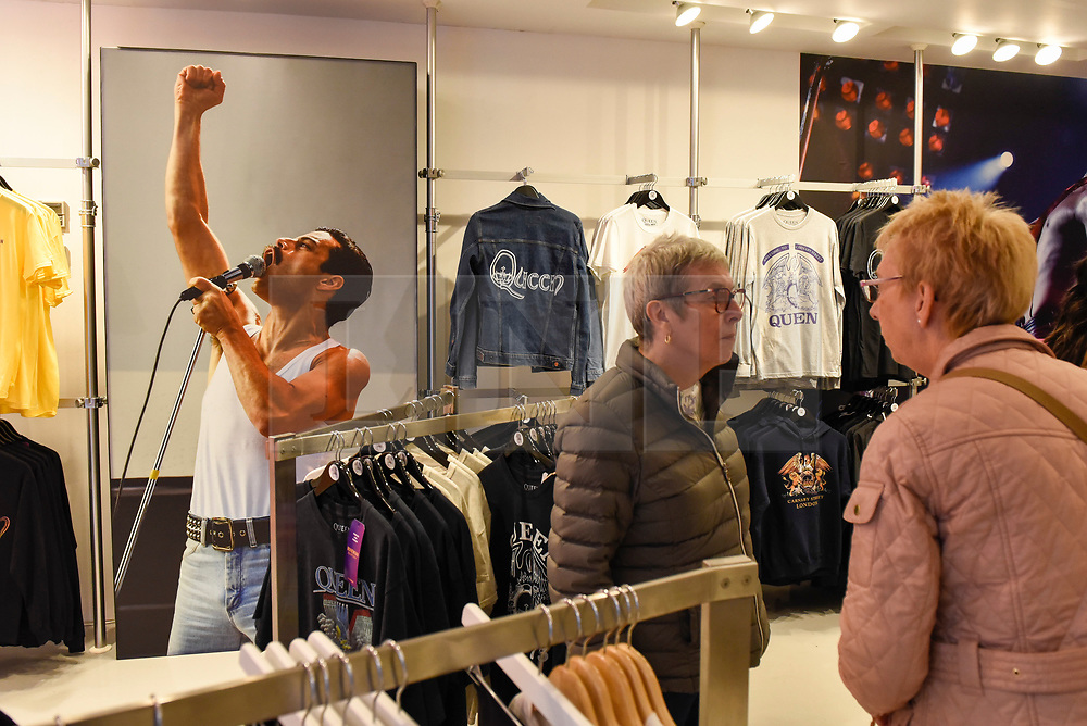 """© Licensed to London News Pictures. 18/10/2018. LONDON, UK.  Visitors to the Queen pop-up shop which has opened in Carnaby Street.  Coinciding with the release next week of the movie """"Bohemian Rhapsody"""", the shop offers Queen music fans memorabilia, a display of stage costumes as well as archived Queen performance footage.  Photo credit: Stephen Chung/LNP"""