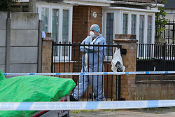 © Licensed to London News Pictures. 17/07/2020. London, UK. A forensic officer in the front garden of a property on Lytton Avenue, Enfield, in north London as police launch a murder investigation following the death of a man in his 30s. Police were called at 04:45hrs early this morning, to a report of four men fighting in Lytton Avenue, Enfield and a man being put into a vehicle. Later the victim died from a single stab wound in North Middlesex Hospital. Three men, no further details, have been arrested on suspicion of murder; all remain in custody. Photo credit: Dinendra Haria/LNP