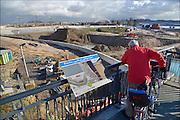 Nederland, Nijmegen, 4-2-2015Aan de overkant van de Waal bij Lent wordt druk gewerkt aan het creeren van een nevengeul in de rivier om bij hoogwater een betere waterafvoer te hebben. Dit zal hier bij de flessenhals Nijmegen 25 tot 30 cm. waterhoogte schelen. Het is een omvangrijk project waarbij onder meer de pijlers van het spoorviaduct een bredere basis moeten krijgen omdat die straks in de loop van het water staan. Ook de n325 die vanaf de Waalbrug naar Arnhem loopt moet over 400 meter opnieuw worden aangelegd omdat het talud vervangen wordt door pijlers. De weg wordt via een bypass tijdelijk omgeleid. Het dorp veurlent komt op een kunstmatig eiland te liggen met twee bruggen als ontsluiting. Een voetgangersbrug en de andere voor normaal verkeer. Een nieuwe kade moet een impuls geven aan evenementen en watersport, pleziervaart. Ruimte voor de rivier, water, waal. In de nieuwe dijk wordt een drempel gebouwd die stapsgewijs water doorlaat en bij hoogwater overloopt. Measures taken by Nijmegen to give the river Waal, Rhine, more space to flow during highwater and to prevent the risk of flooding. Room for the river. Reducing the level, waterlevel. Foto: Flip Franssen/Hollandse Hoogte