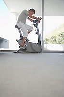 Mature man on exercise bike pedalling side view